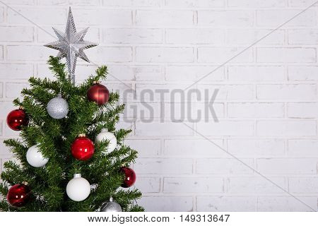 Close Up Of Christmas Tree Over White Brick Wall