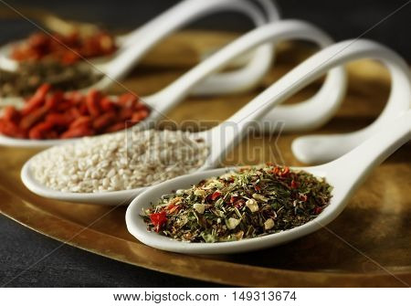 Different spices in spoons on tray