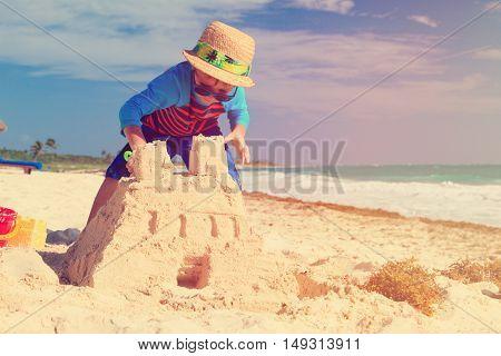 little boy building sandcastle on tropical sand beach