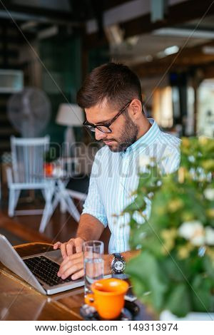 Handsome man working on a computer in a cafe.