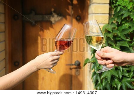 Hands holding glasses with wine on wooden door background