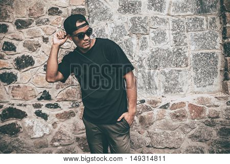 Feeling comfortable in his style. Handsome young African man in casual clothes adjusting his cap and keeping one hand in pocket while standing against the stoned wall outdoors