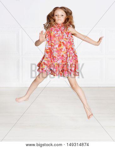 portrait of cute little girl posing in pink dress