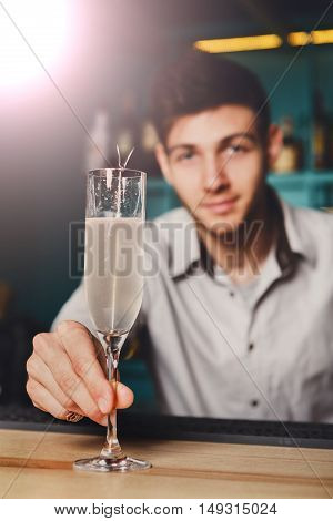Young handsome Barman offers champagne glass in night club. Professional male bartender at work in bar made an alcohol drink for party. Focused on glass