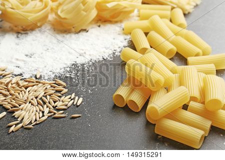 Different dry pasta with flour on grey table