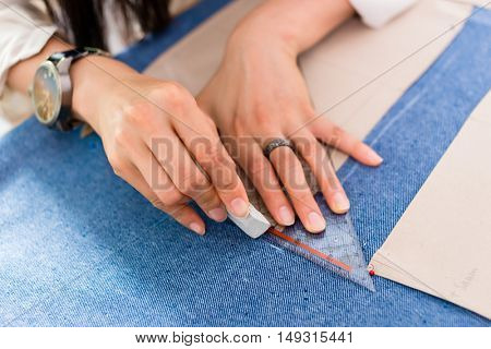 Detail of hands with scissors at tailor shop cutting cloth