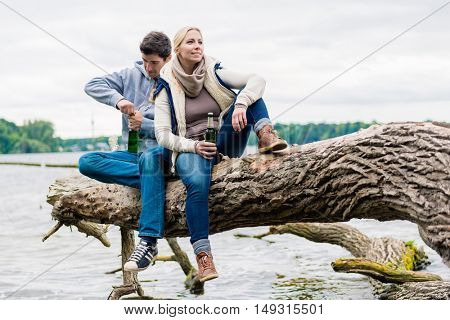 Man and woman sitting on trunk near at lakeside and drinking bottled beer