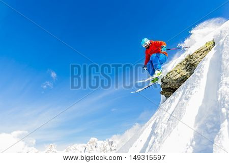 Man skiing in fresh powder snow in Italians Alps, captured jump in flight in high mountains.