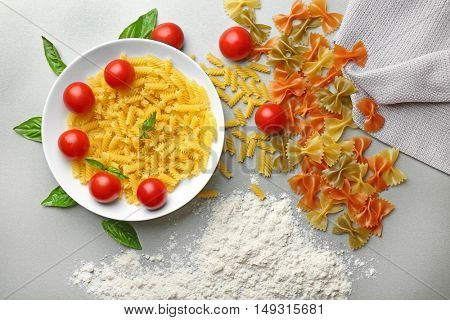 Plate with different kinds of pasta with cherry tomatoes on table