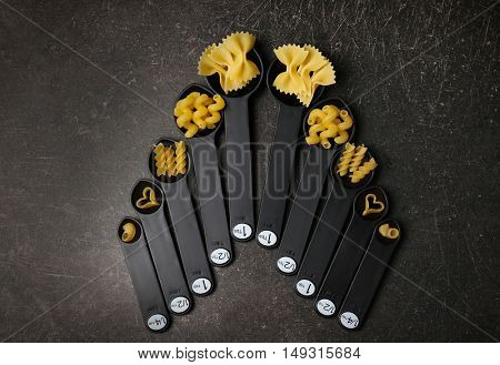Different dry pasta on measuring spoons