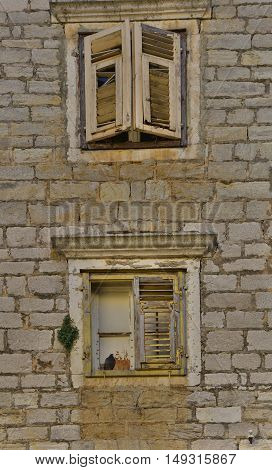 Windows in an old historic building in the small town of Skradin on the coast of the Sibenik-Knin County of Croatia