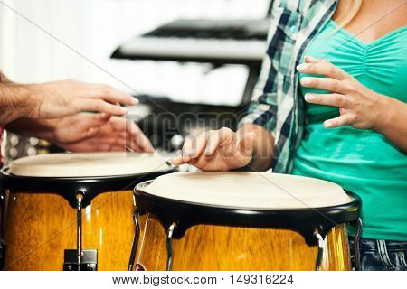 Musicians playing congas in music store. Close up.