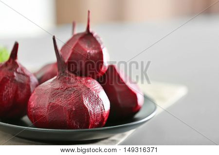 Plate with fresh beetroot on table
