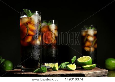 Kitchen board with cuba libre cocktails, knife, mint and lime on dark background