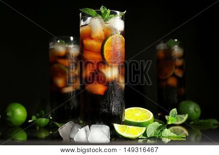 Cuba libre cocktail with mint, ice and lime on dark background