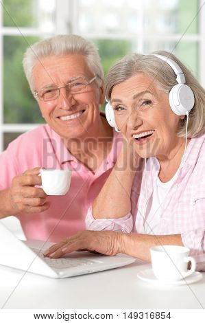 Senior couple portrait with laptop and coffee at home