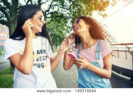 Laughing female friends listen to music while sharing ear buds on running path