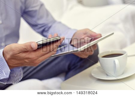 a young caucasian businessman checking his smartphone and his tablet sitting next to a table with a cup of coffee on it