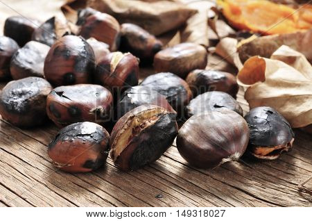 closeup of some roasted chestnuts on a rustic wooden table with some roasted sweet potatoes and autumn leaves in the background