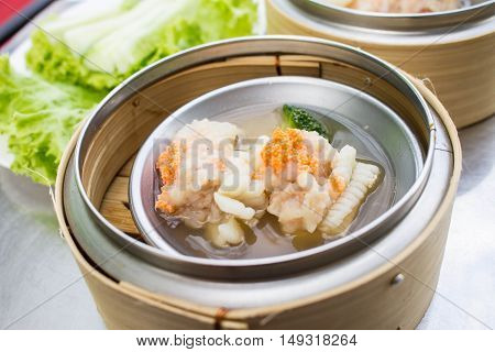 dim sum - steamed Minced pork with squid and Shrimp eggs in bamboo basket on table blur background