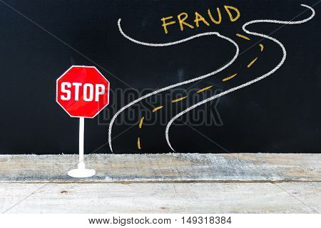 Mini Stop Sign On The Road To Fraud