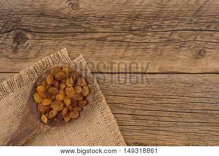 Raisins in wooden spoon on old wooden table. Top view.