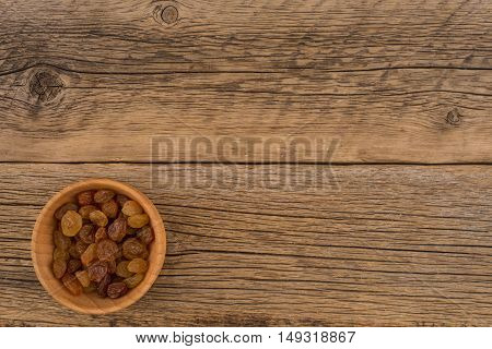 Raisins in a wooden bowl on the old wooden table. Top view.
