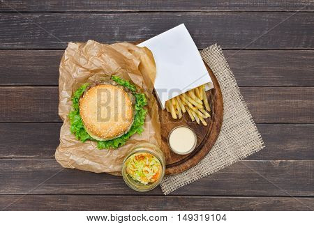 Fast food dish top view. Meat burger, potato chips on wood. Takeaway composition. Wrapped French fries, hamburger, mayonnaise sauce on wooden desk.