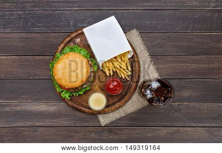 Fast food dish top view. Meat burger, potato chips and glass of cola drink with ice on wood. Takeaway composition. Wrapped French fries, hamburger, mayonnaise and ketchup sauces on wooden desk.