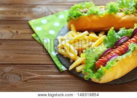 Delicious hot dog and fries on round wooden board