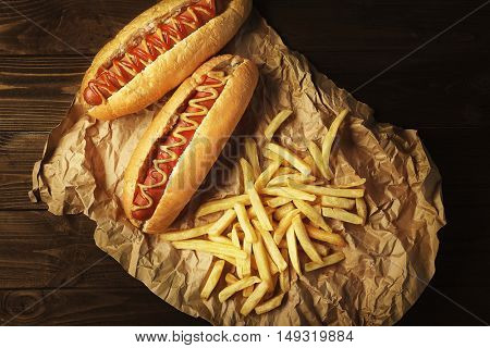 Tasty hot dogs and fries on wooden background