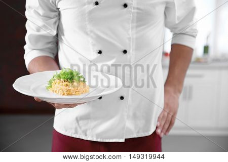 Young handsome chef cook with pasta on plate