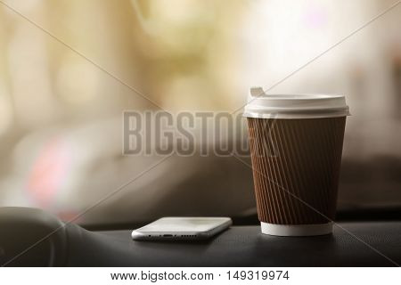Cup of coffee and smartphone on car console