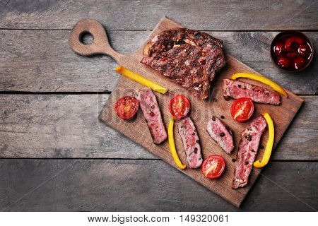 Tasty grilled steak with vegetables on cutting board