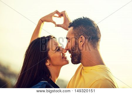 Couple enjoying sunset and making hearts by hands.