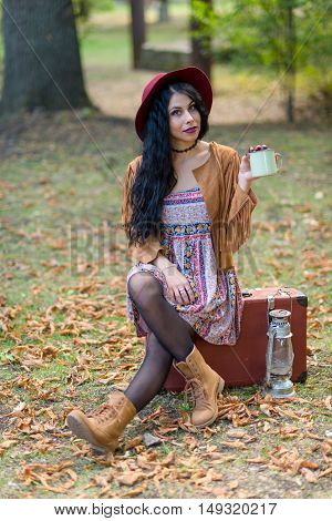 Smiling happily hipster girl goes along the autumn field with vintage suitcase. Concept-expectation of traveling. Toned image.
