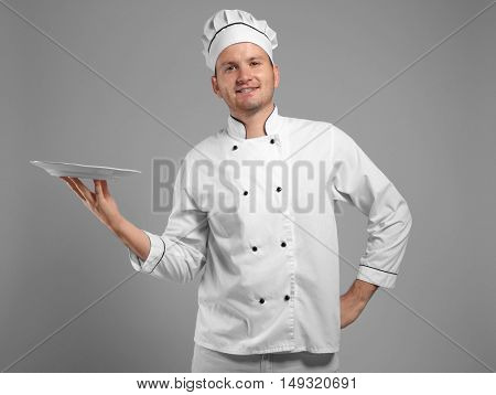 Young chef cook holding plate on grey background