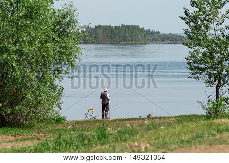 a single fisherman catches a fish on the shore