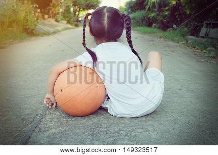preschool girl with basketball sitting on street