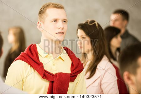 Picture of young man standing alone in the crowd