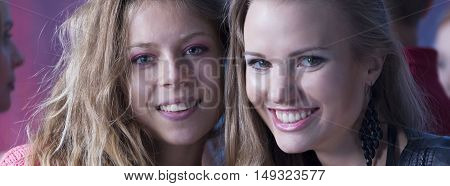 Closer shot of two young woman standing close and smiling