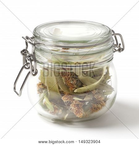 Dried linden flower in a closed jar isolated on white background. The flowers resemble miniature umbrellas with yellowish color have a strong flavor and are used for making tea.