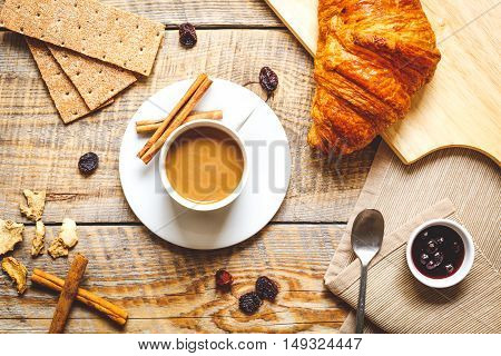 breakfast at home on wooden table with cup of milk coffee, croissants, macaroon, crackers and empty blank notebook