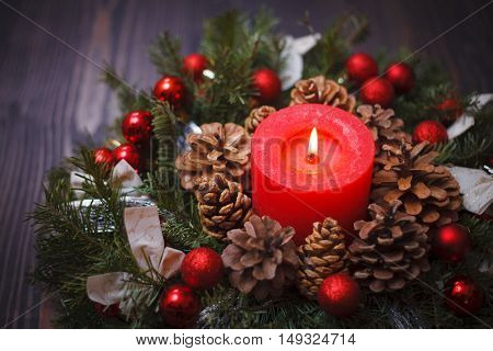 Decorated Christmas wreath with a candle close-up on a wooden background