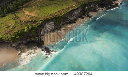 Aerial photo from flying drone of an amazing nature scenery with rock cliff on sandy coastline. Beautiful sea water with waves for surfing in summer season in Bali. Beauty Indian ocean landscape