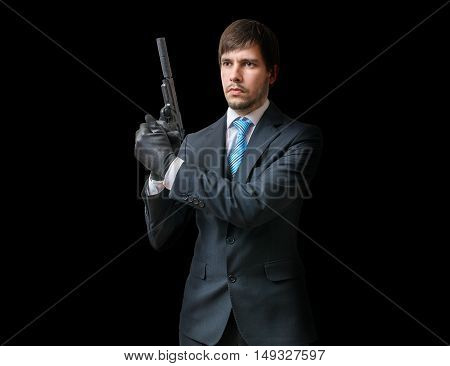 Main In Suit Holds Pistol With Silencer In Hands On Black Backgr