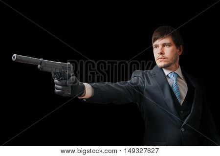 Agent Is Aiming With Pistol With Silencer On Black Background. L
