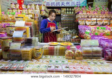 JIUFEN TAIWAN - 23 February 2016 - Female candy shop seller checks her goods in Jiufen Taiwan on February 23 2016
