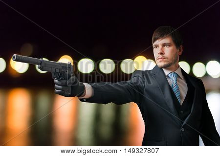 Agent Or Hitman Is Aiming With Pistol With Silencer At Night.