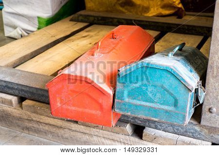 grunge red and blue metal tool boxes on wood palette in factory.